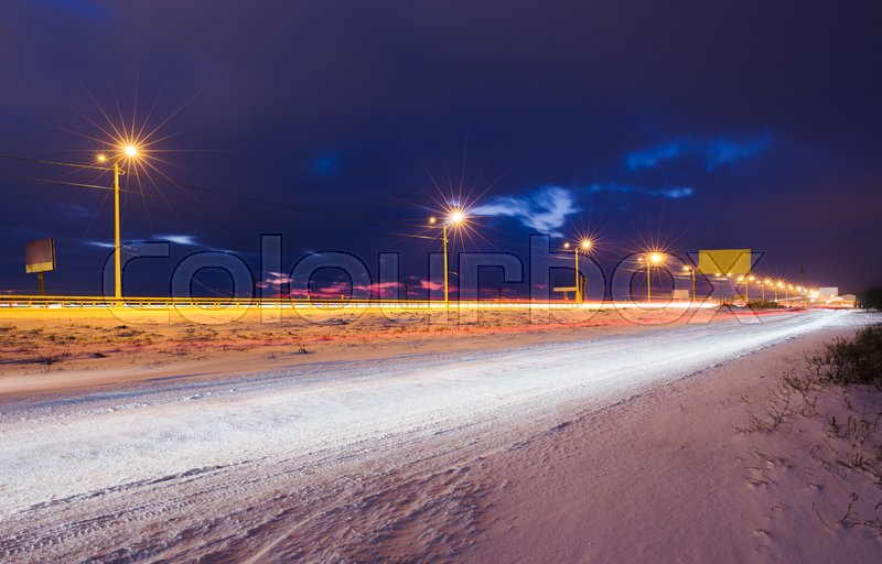Winter snowy highway at night shined with lamps, stock photo