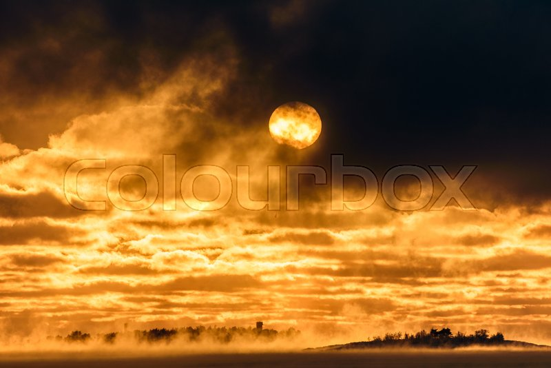 Sun appear through dark clouds above Baltic Sea that is about to freeze over with islands in horizon and sea smoke rising from the sea water, stock photo
