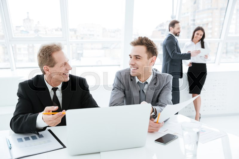 Laughing Business partners sitting by the table with laptop and documents with colleagues on background, stock photo
