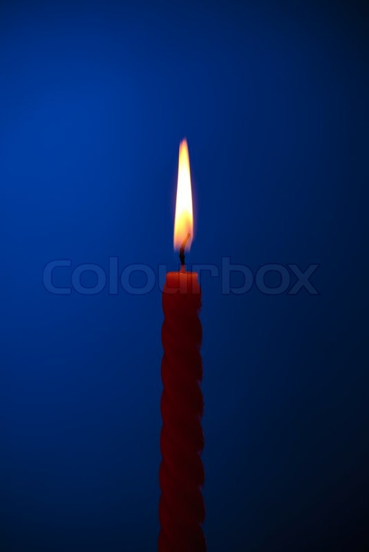 Single Twisted Burning Candle Over Blue Background Stock