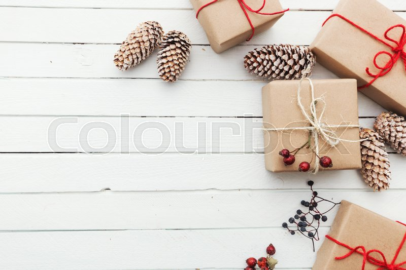Homemade wrapped rustic brown paper packages with various natural things on white wooden surface, stock photo