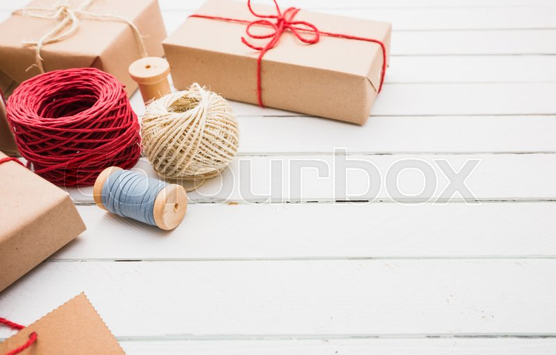 Homemade wrapped rustic brown paper packages on white wooden surface, stock photo