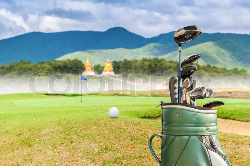 Golf equipment,golf ball and golf bag on green and hole as background, stock photo