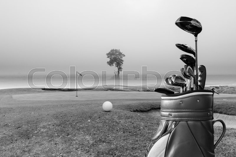Golf equipment,golf ball and golf bag on green and hole as background.black and white, stock photo