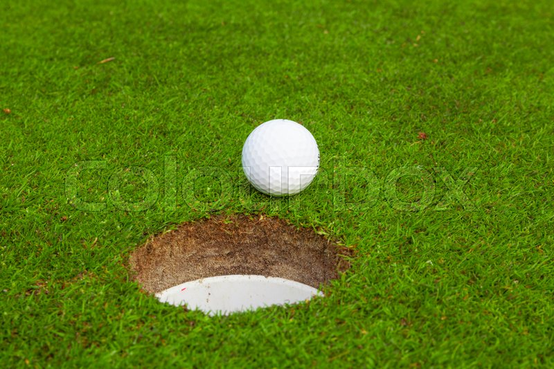 Golf ball on lip of cup. Golf ball on green grass in golf course, stock photo