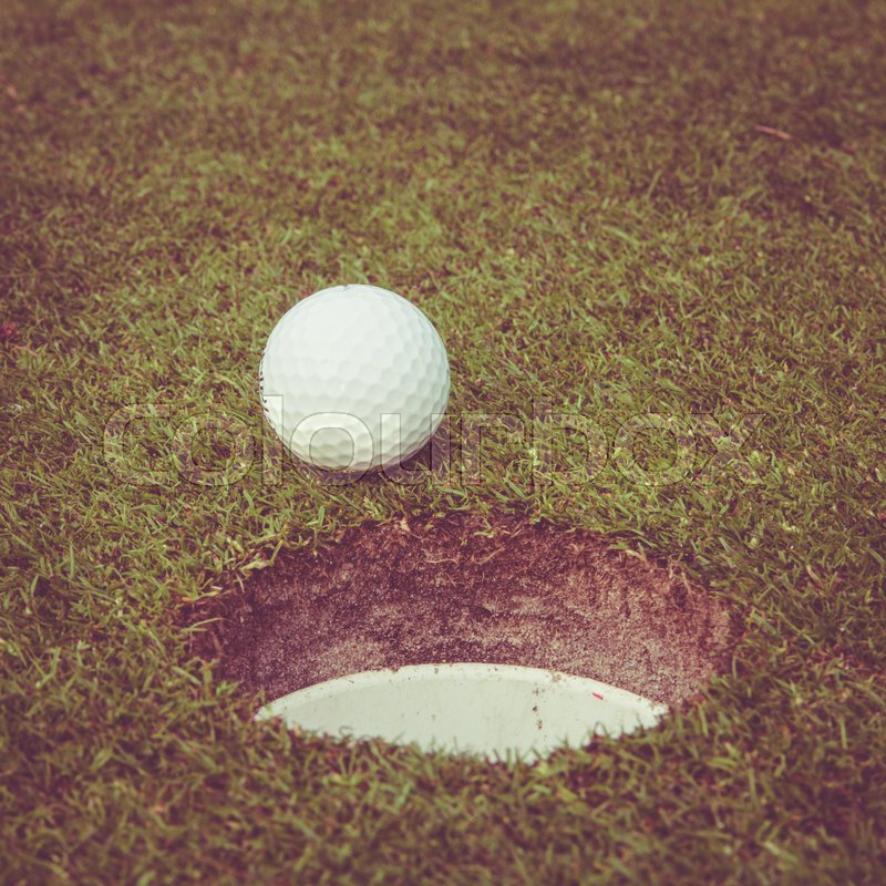 Golf ball on lip of cup. Golf ball on green grass in golf course. Vintage, retro style, stock photo