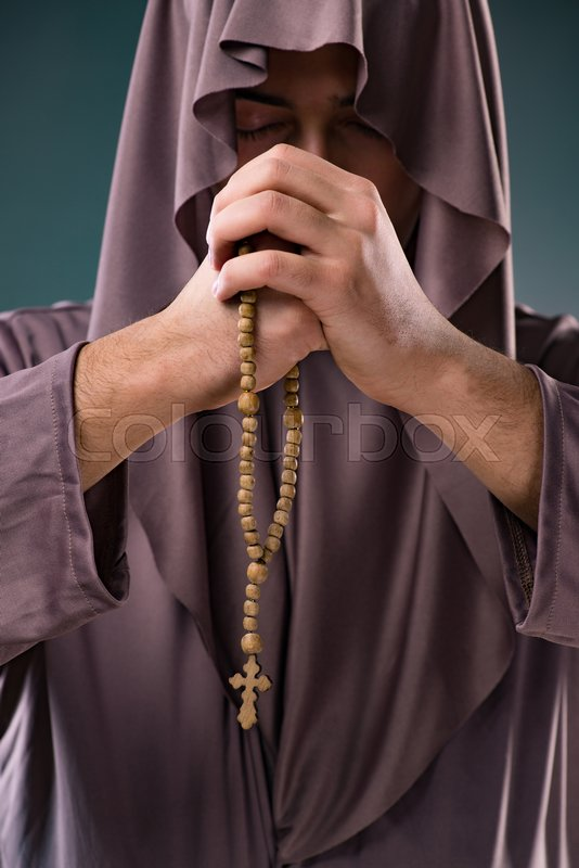 Monk in religious concept on gray background, stock photo