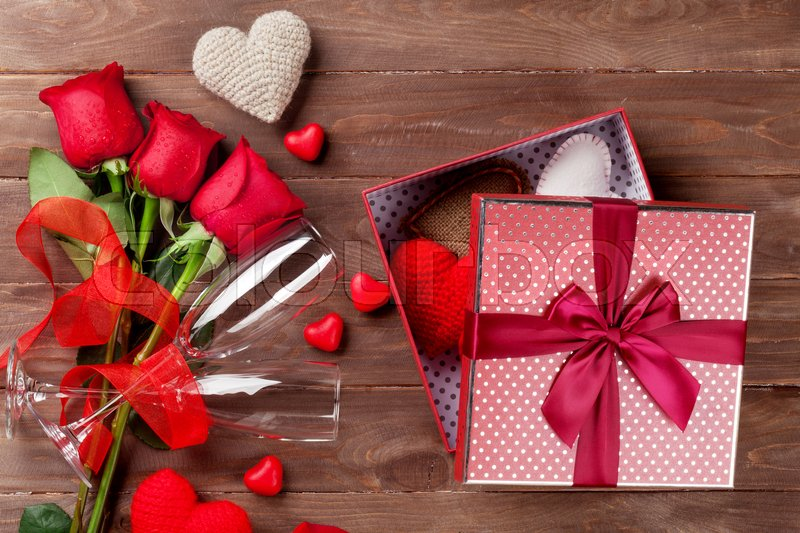Valentines day gift box with hearts, red roses and champagne glasses on wooden table. Top view, stock photo