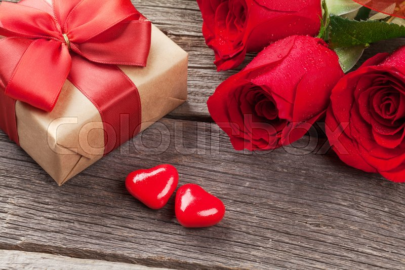 Valentines day gift box, roses and candy hearts over wooden table, stock photo