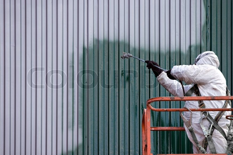 A Commercial Painter On An Industrial Lift Spray Painting