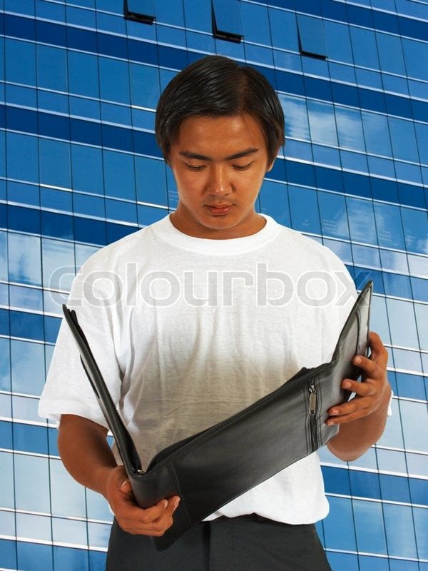 Stock Bild von 'Worker Checking Seine Noten in einer Ledermappe'
