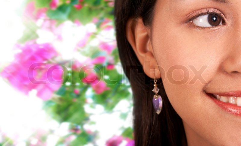 Stock Bild von 'Smiling Beautiful Girl With Flowers Hintergrund'