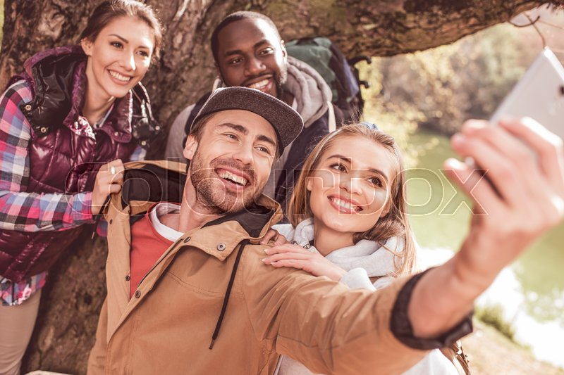 Group of young people standing near huge tree and taking selfie near calm forest river, stock photo