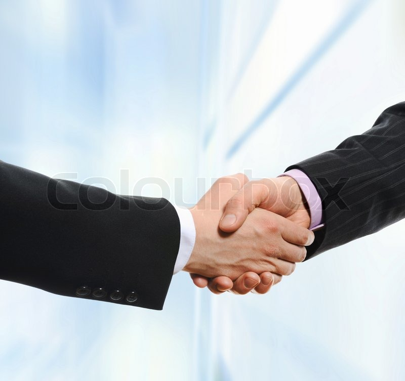 Stock image of 'Handshake of business partners on the background of an office building'