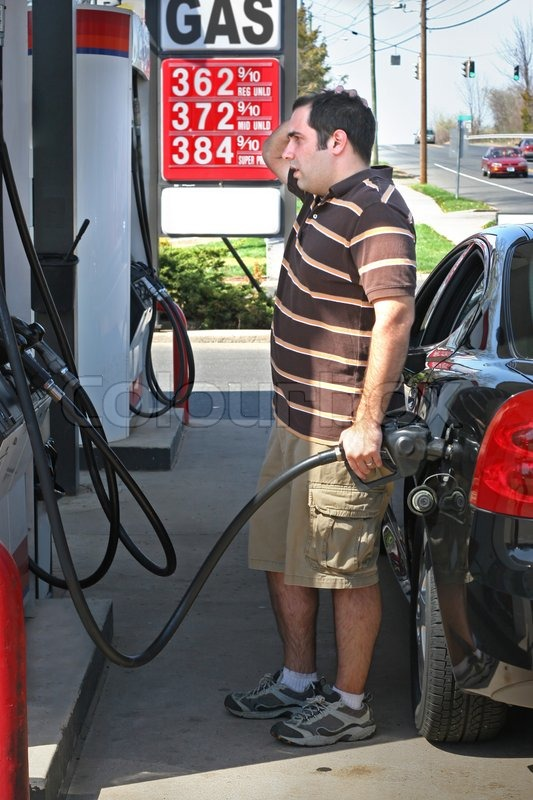 A Man Pumping High Priced Gas Into His Car With A