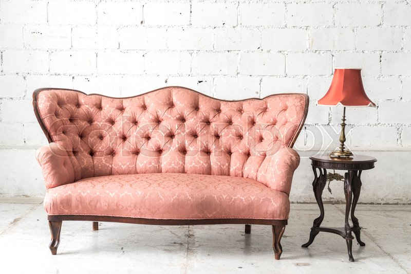 Pink vintage sofa and lamp on white wall, stock photo
