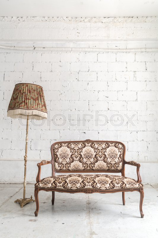 Brown vintage sofa and lamp on white wall, stock photo