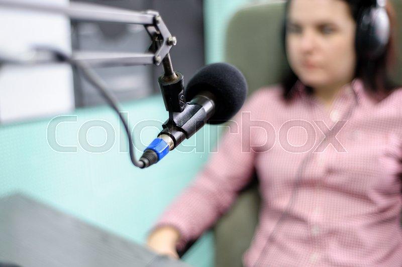 A radio DJ announces news in a radio-studio, stock photo