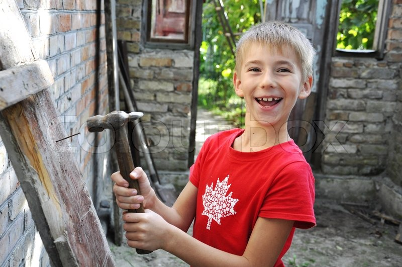 Wonderful Little Boy With A Hammer Helping His Parents Build A House, Stock Photo