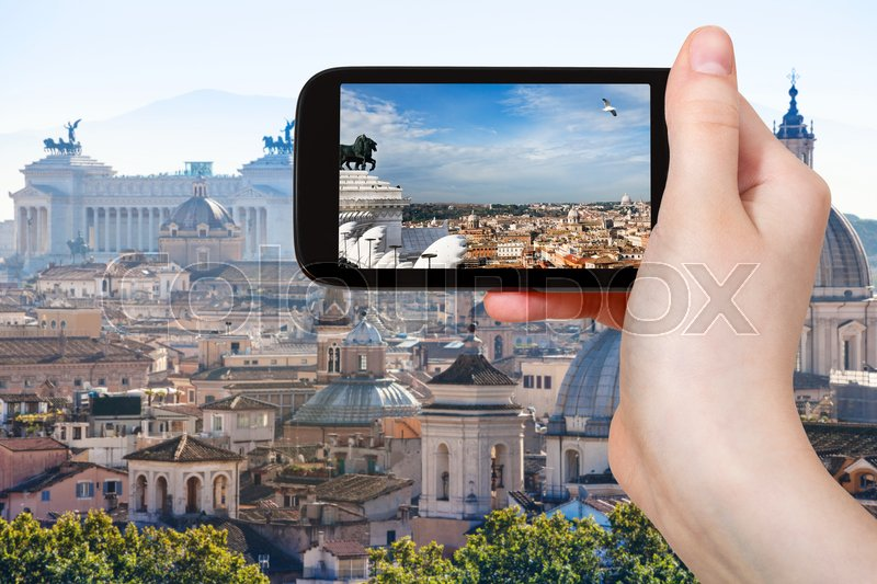 Travel concept - tourist photographs Rome skyline on smartphone in Italy, stock photo
