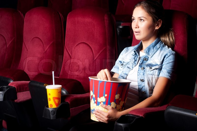 young woman sitting alone in the cinema and watching a