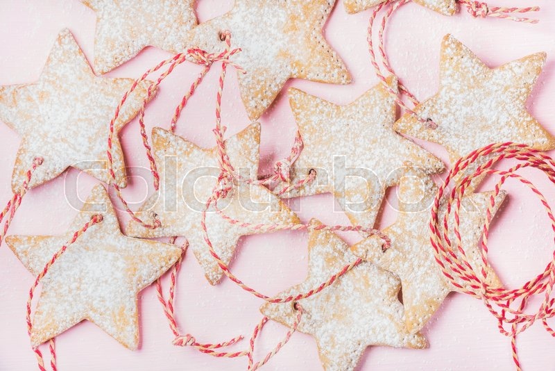 Close-up of Christmas homemade gingerbread star shaped cookies with sugar powder and red decoration rope over light pink background, top view, horizontal composition, stock photo