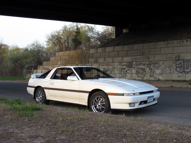 A Shot Of A White Japanese Sports Car Underneath A Graffiti Covered Highway  Overpass, Stock Photo