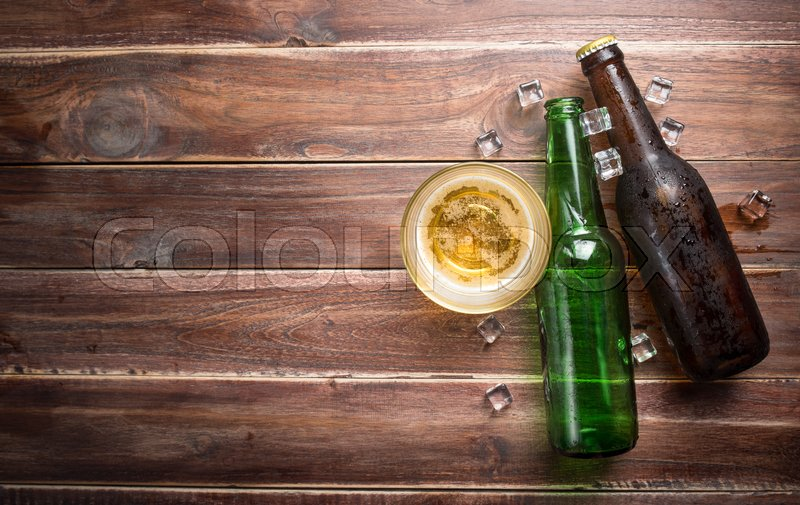 Beer glass with bottle cap and bottle on rustic wood background,space for text,top view, stock photo