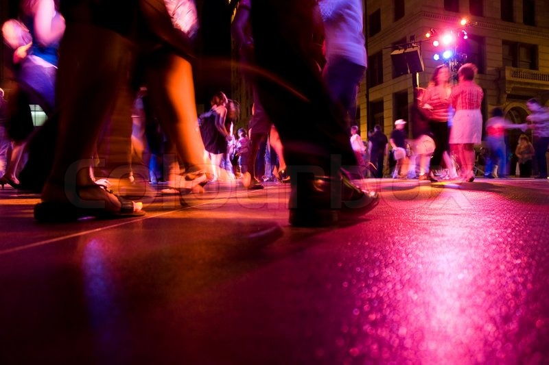 A low shot of the dance floor with people dancing under the colorful lights, stock photo