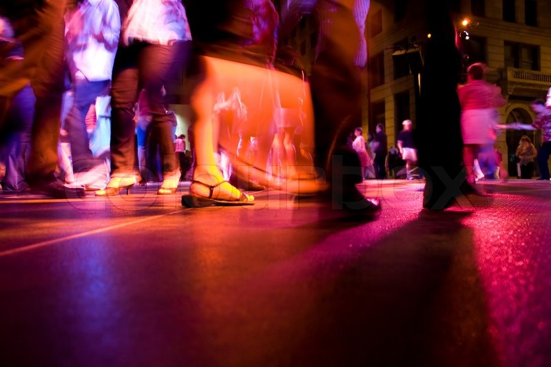 Stock image of 'A low shot of a dance floor with people dancing under the colorful lights'