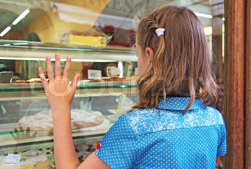 Little girl dreaming of sweets and cakes, stock photo