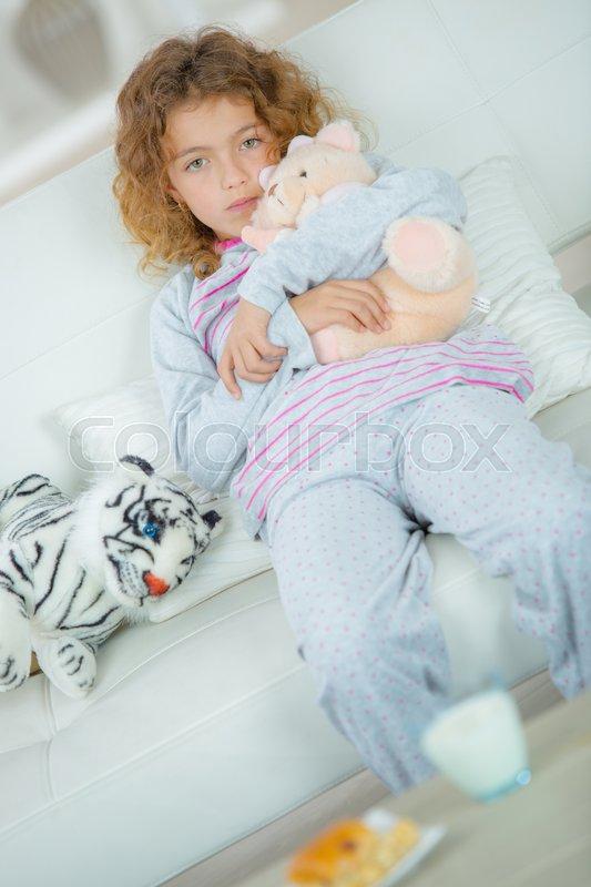 School Girl On Sofa Cuddling Soft Toy, Stock Photo