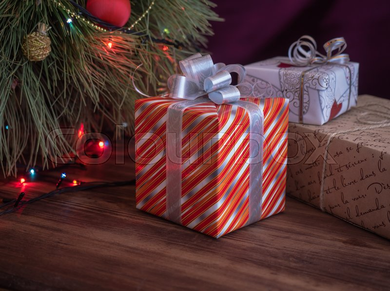 Green Christmas tree decorated with toys and garland with led lights. Boxes with gifts. Christmas present in boxes at wooden table. Green fir tree with toys and gifts under the tree, stock photo