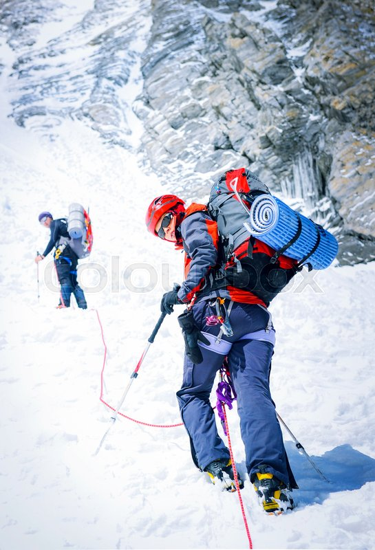 Team of two alpinists climbing a mountain. Extreme sport concept, stock photo