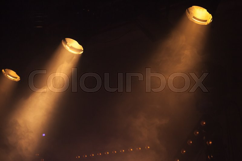 Scenic spot lights with bright beams in smoke, stage illumination, stock photo