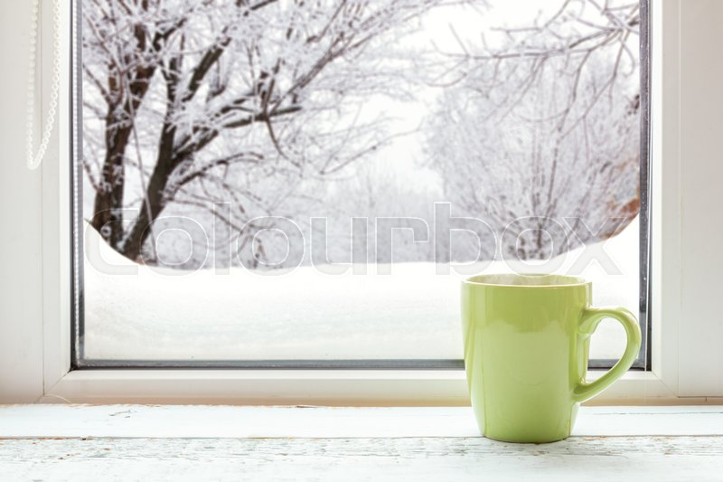 Cup of coffee on the window sill. In the background, a beautiful winter landscape in snow. Cozy home concept, stock photo