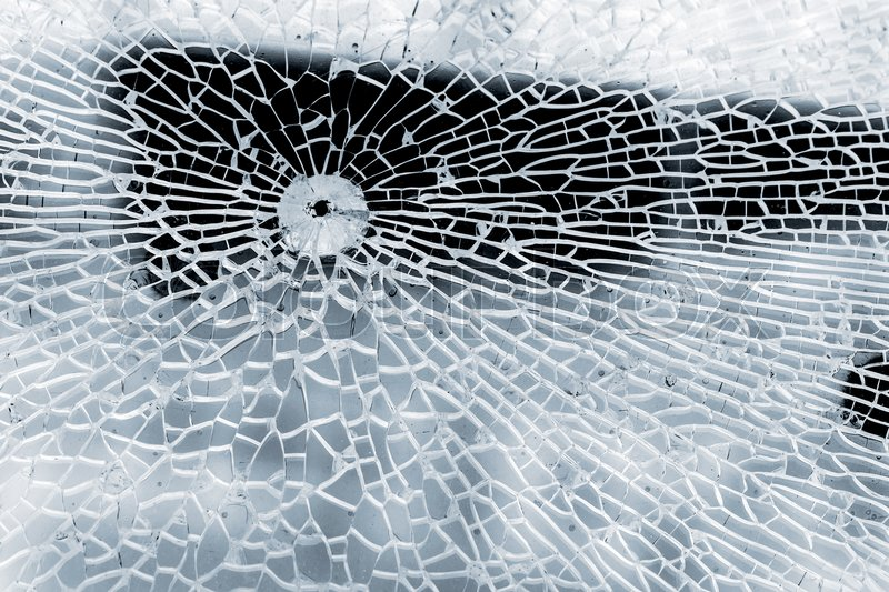 Broken strained glass with bullet hole and craks. Close-up background photo texture, stock photo