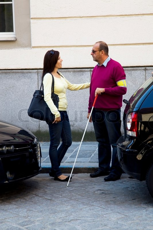 A Young Woman Helps A Blind Man Across The Street Stock