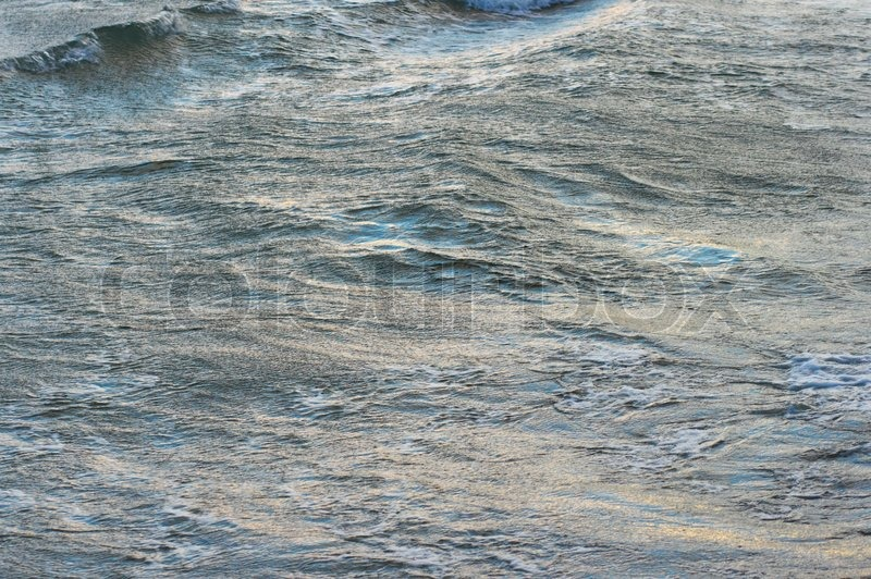 Evening sea waving surface with blue (sky) reflections and yellow (evening sun), stock photo