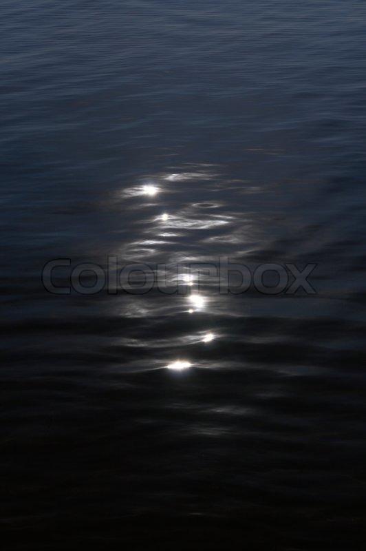 Moon catchlights on night sea water surface, stock photo
