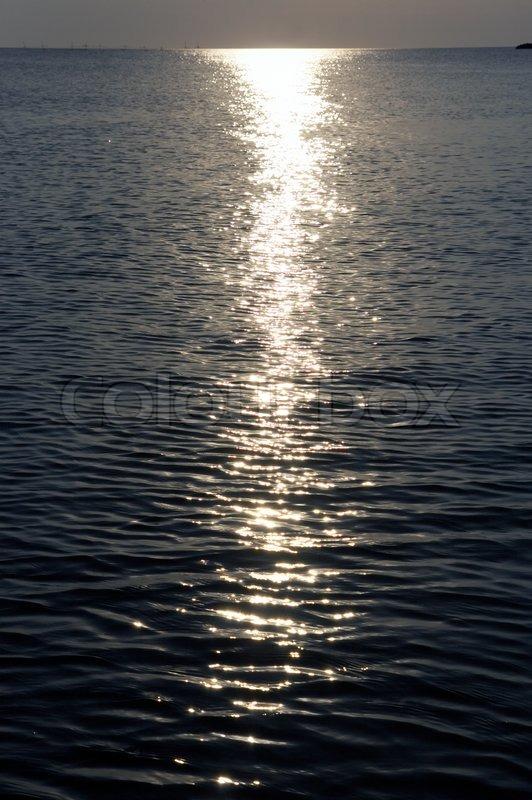 Moonlight path on night sea water surface, stock photo