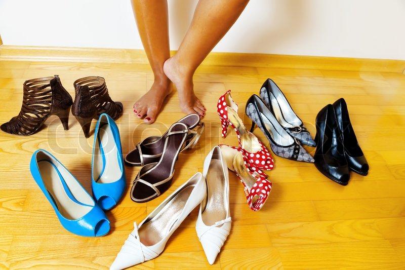 b0991712bba Stock foto af 'En ung kvinde har mange forskellige sko at vælge imellem'