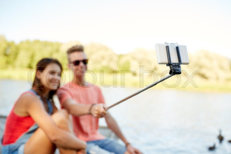 Technology, vacation and people concept - happy teenage couple taking picture by smartphone selfie stick and sitting on river berth at summer, stock photo