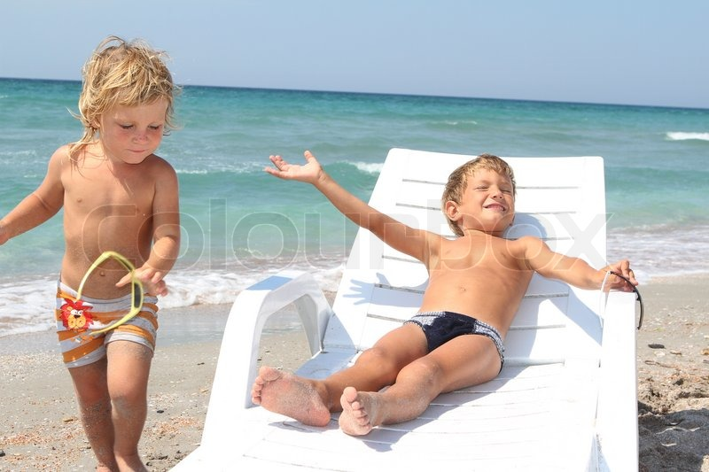 two children relaxing on beach stock photo colourbox