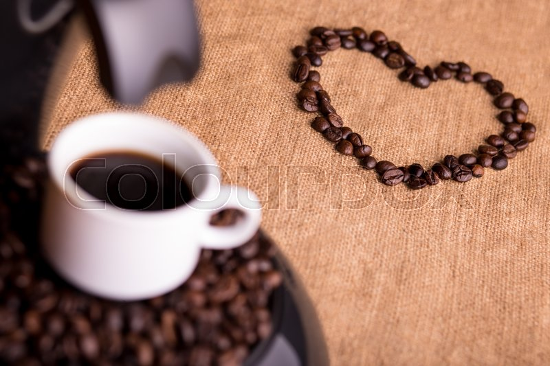 Cup of strong coffee on a coffee maker and heart made of coffee beans, stock photo
