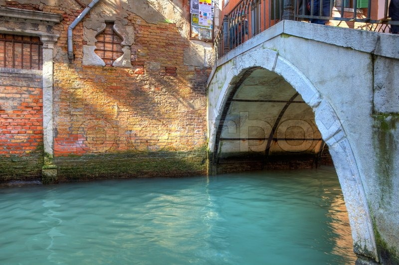 Small Canal Flow Along Old Brick Walls Under Vintage Bridge In Venice Italy Stock Photo