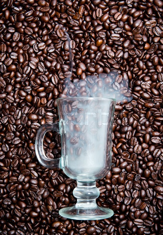Irish coffee glass stuck in fresh coffee beans. Smoke is coming out of the glass, stock photo