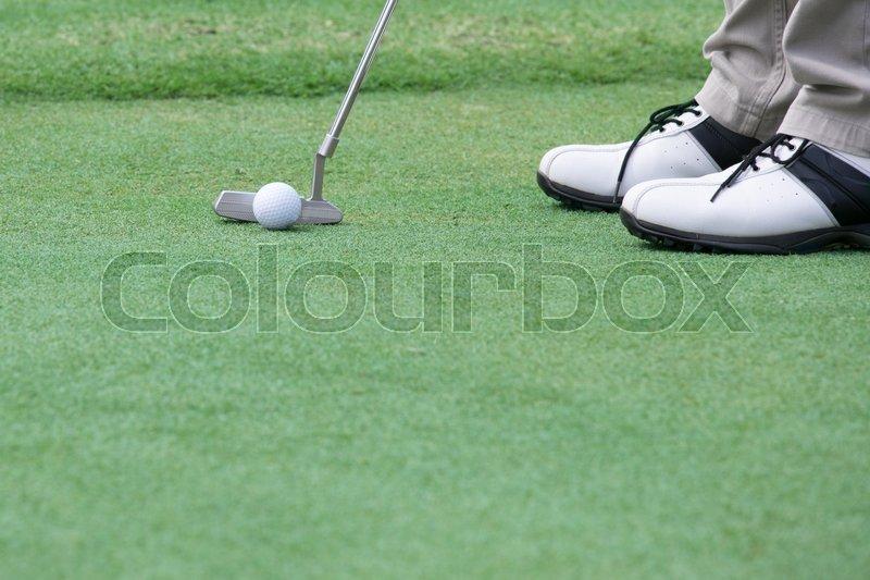 Golf player put a golf ball on a green, stock photo