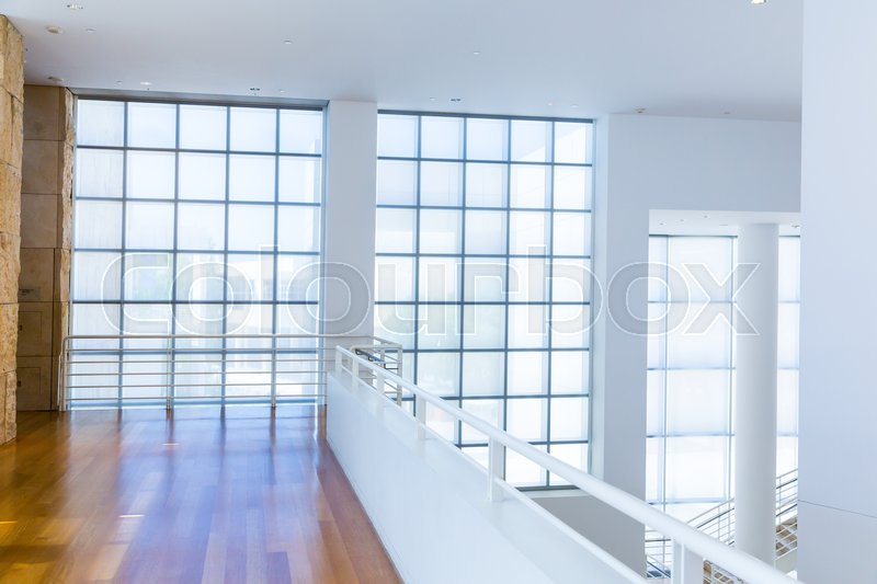 Balcony with wooden floor against glass block wall. White tones style, stock photo