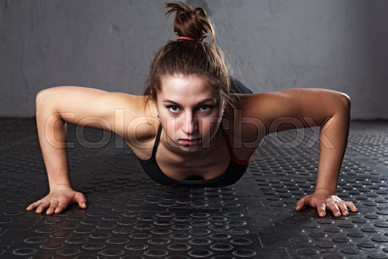 Fitness woman doing push-ups in the gym, close-up, stock photo